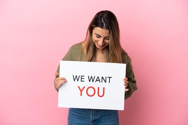 Jonge blanke vrouw geïsoleerd op roze achtergrond met we want you board