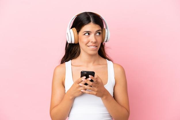 Jonge blanke vrouw geïsoleerd op roze achtergrond muziek luisteren met een mobiel en denken