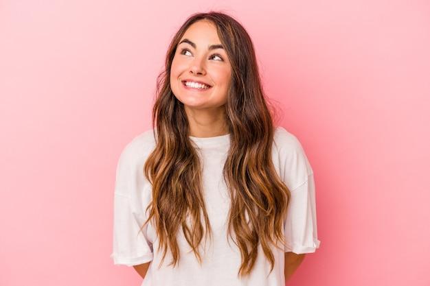 Jonge blanke vrouw geïsoleerd op roze achtergrond ontspannen en gelukkig lachen, nek uitgerekt met tanden.
