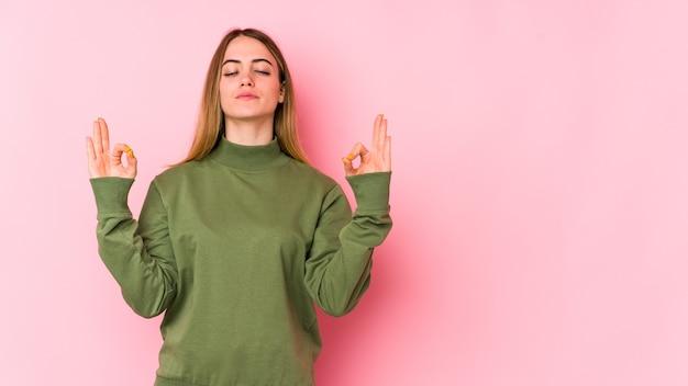 Jonge blanke vrouw geïsoleerd op roze achtergrond ontspant na een zware werkdag, ze presteert yoga.