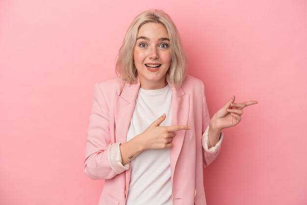 Jonge blanke vrouw geïsoleerd op roze achtergrond opgewonden wijzend met wijsvingers weg.
