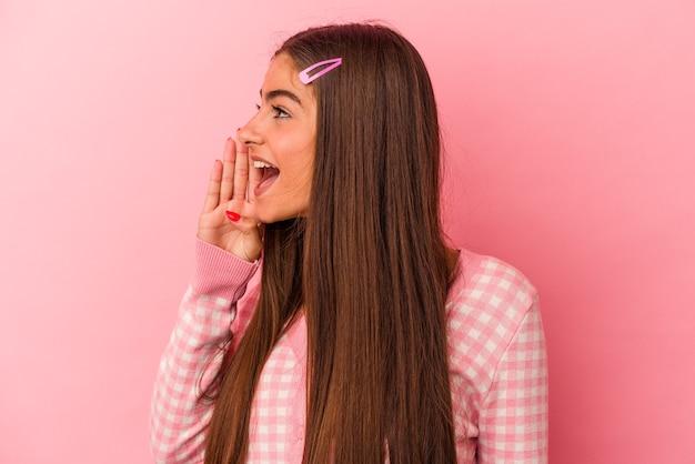 Jonge blanke vrouw geïsoleerd op roze achtergrond schreeuwen en houden palm in de buurt van geopende mond.
