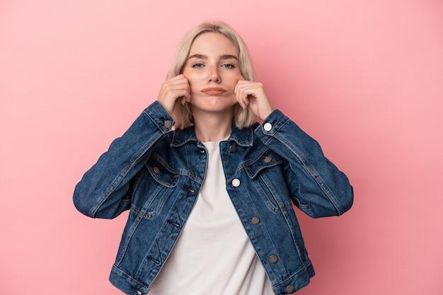 Jonge blanke vrouw geïsoleerd op roze achtergrond twijfelen tussen twee opties.