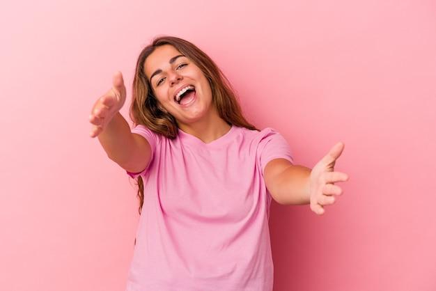 Jonge blanke vrouw geïsoleerd op roze achtergrond voelt zich zelfverzekerd en geeft een knuffel aan de camera.