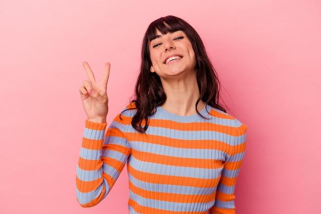 Jonge blanke vrouw geïsoleerd op roze achtergrond vrolijk en zorgeloos met een vredessymbool met vingers.