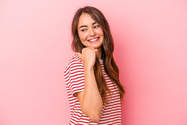Jonge blanke vrouw geïsoleerd op roze achtergrond wijst met duimvinger weg, lachend en zorgeloos.