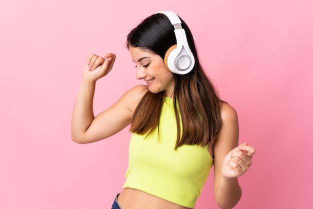 Jonge blanke vrouw geïsoleerd op roze muur luisteren muziek en dansen