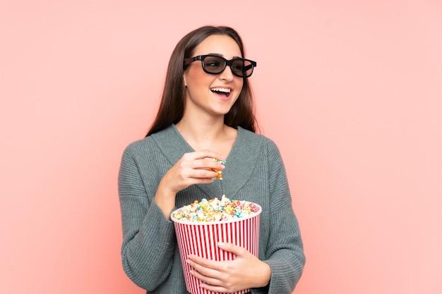 Jonge blanke vrouw geïsoleerd op roze muur met 3d-bril en met een grote emmer popcorns