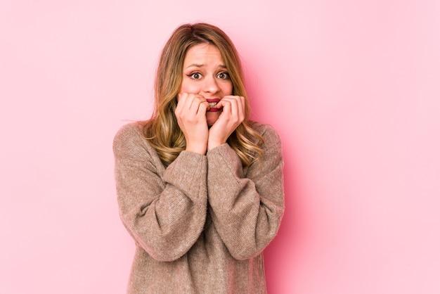 Jonge blanke vrouw geïsoleerd op roze vingernagels bijten, nerveus en erg angstig.