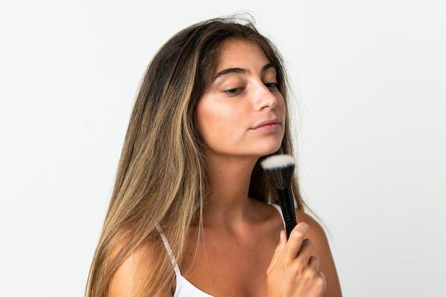 Jonge blanke vrouw geïsoleerd op wit make-up borstel en denken te houden