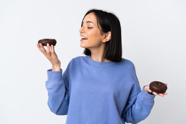 Jonge blanke vrouw geïsoleerd op wit met donuts met gelukkige uitdrukking