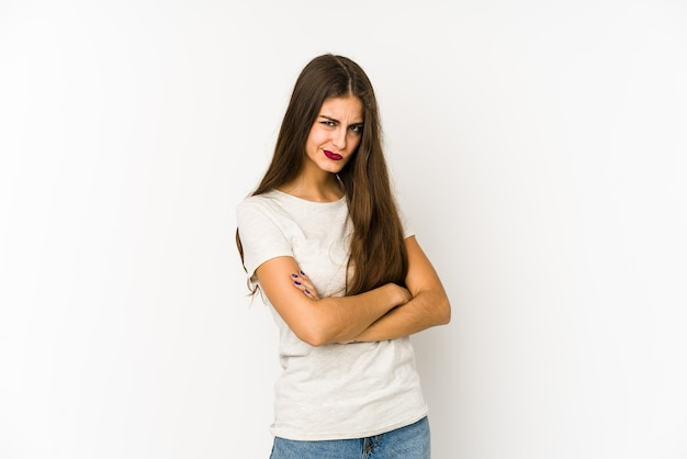 Jonge blanke vrouw geïsoleerd op witte ruimte fronsend gezicht in ongenoegen, houdt armen gevouwen.