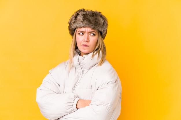 Jonge blanke vrouw, gekleed in een winterkleren geïsoleerd fronsend gezicht in ongenoegen, houdt armen gevouwen.