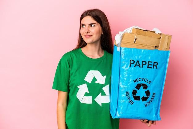 Jonge blanke vrouw gerecycled karton geïsoleerd op roze muur droomt van het bereiken van doelen en doeleinden