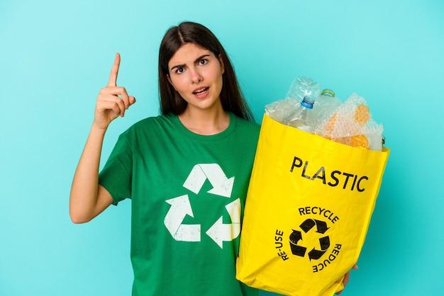 Jonge blanke vrouw gerecycled plastic geïsoleerd op blauwe achtergrond met een idee, inspiratie concept.