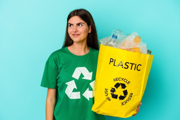 Jonge blanke vrouw gerecycled plastic geïsoleerd op blauwe muur droomt van het bereiken van doelen en doeleinden