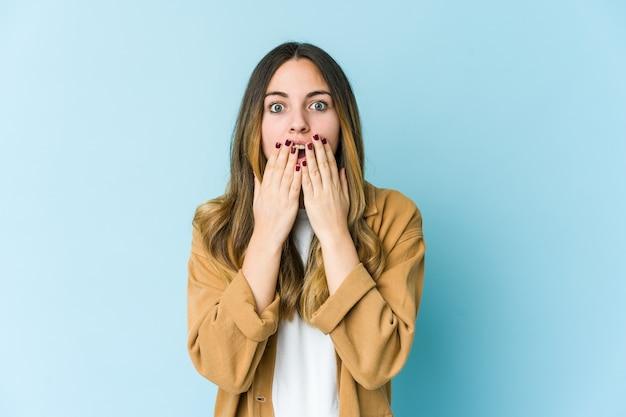 Jonge blanke vrouw geschokt, mond bedekt met handen, angstig om iets nieuws te ontdekken.