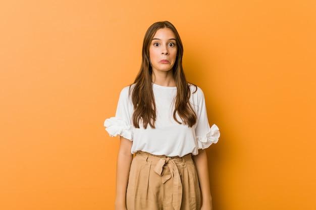 Jonge blanke vrouw haalt schouders en verwarde ogen op.