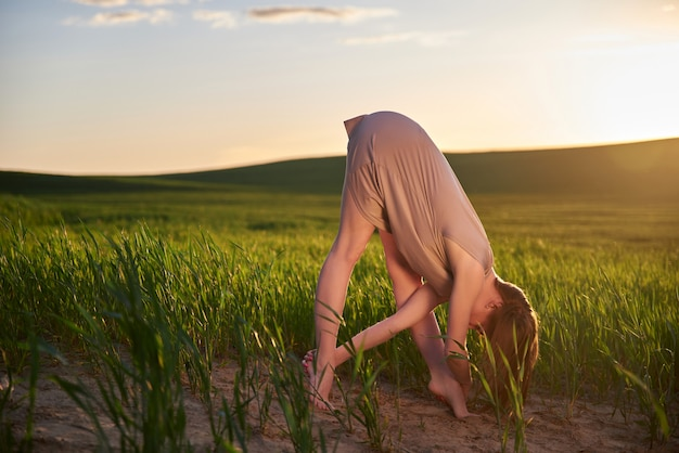 Jonge blanke vrouw het beoefenen van yoga, in de natuur in een veld van groen gras in de zomer bij zonsondergang. rekken, meditatie, zonne-energie. kunsttherapie, ontspanning.