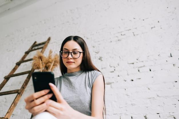 Jonge blanke vrouw in bril met behulp van mobiele telefoon in de buurt van witte bakstenen muur binnen