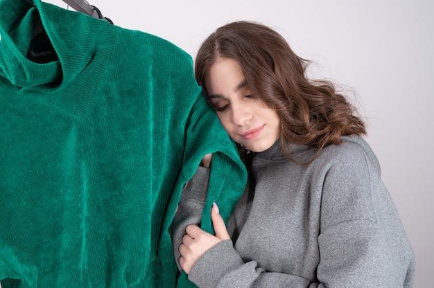 Jonge blanke vrouw in de winkel onderzoekt en kiest kleding