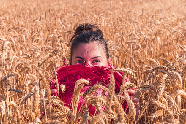 Jonge blanke vrouw in een mooie rode jurk die geniet van het zonnige weer in een tarweveld