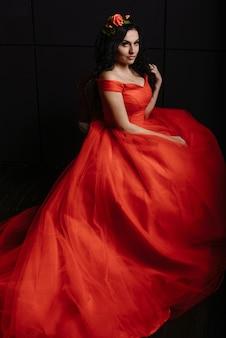 Jonge blanke vrouw in een vintage rode jurk op een zwarte.