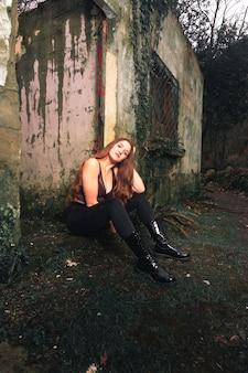 Jonge blanke vrouw in het bos met een verlaten gebouw erachter