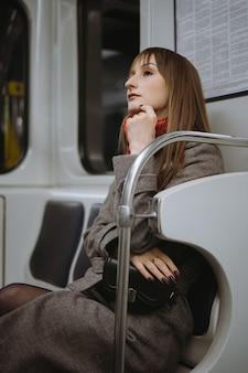 Jonge blanke vrouw in jas zit alleen in de metro en kijkt dromerig opzij