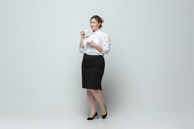 Jonge blanke vrouw in kantoorkleding op grijze muur