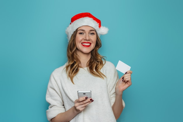 Jonge blanke vrouw in kerstmuts en witte winter trui glimlachen, mobiele telefoon en creditcard te houden