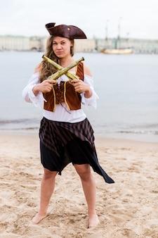 Jonge blanke vrouw in piraat kostuum gekruist speelgoed geweren voor haar.
