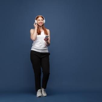 Jonge blanke vrouw in vrijetijdskleding, luisteren naar muziek