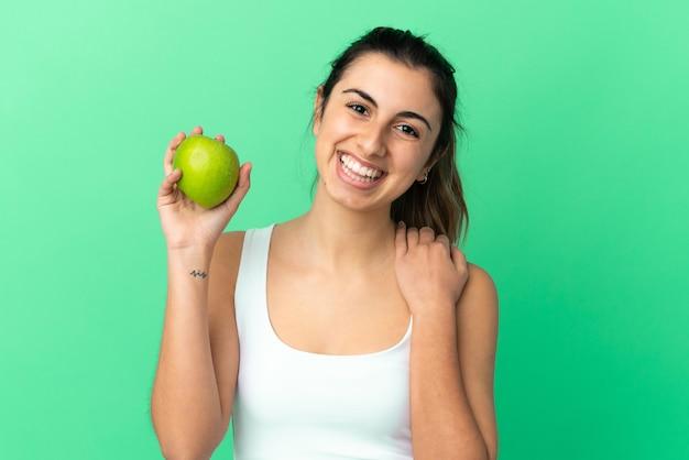 Jonge blanke vrouw isoleerde groene achtergrond met een appel en happy