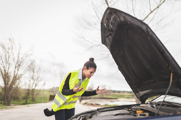 Jonge blanke vrouw kijken naar auto-motor, ze weet niet wat ze moet doen, auto kapot op het midden van de weg. auto en hulp bij pech onderweg.