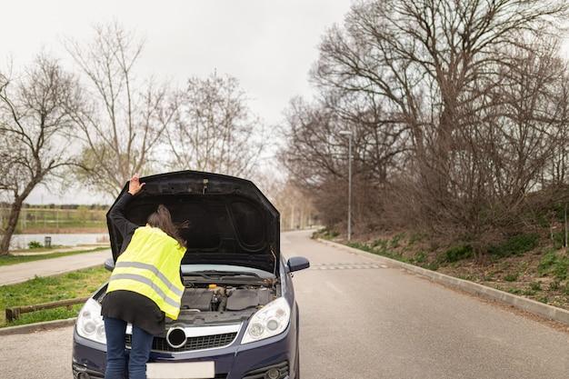 Jonge blanke vrouw kijken naar motor van een auto, auto opgesplitst in het midden van de weg. auto en hulp bij pech onderweg.