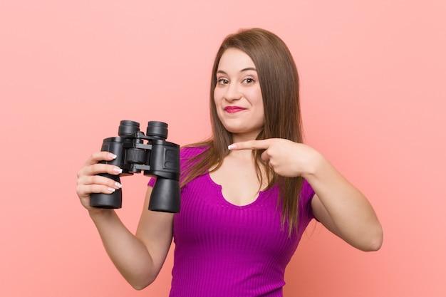 Jonge blanke vrouw kijkt door een verrekijker