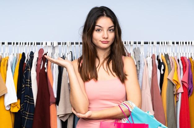 Jonge blanke vrouw kopen wat kleren in een winkel ongelukkig voor iets niet begrijpen