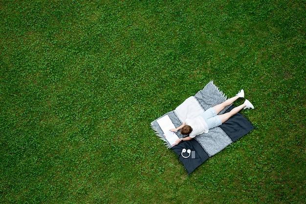 Jonge blanke vrouw liggend op de deken op groen gazon en het lezen van een boek