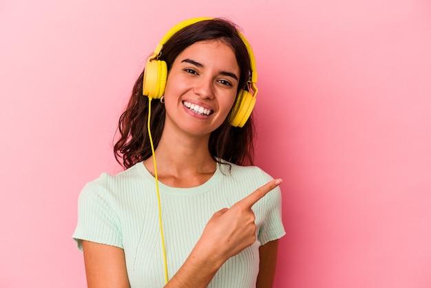 Jonge blanke vrouw luisteren muziek geïsoleerd op roze achtergrond glimlachend en opzij wijzend, iets tonen op lege ruimte.