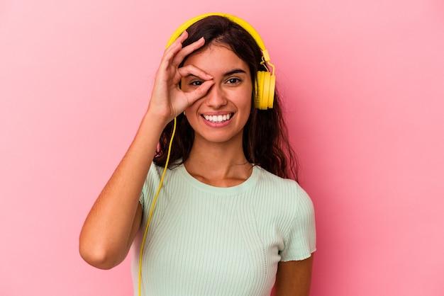 Jonge blanke vrouw luisteren muziek geïsoleerd op roze achtergrond opgewonden houden ok gebaar op oog.