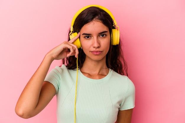 Jonge blanke vrouw luisteren muziek geïsoleerd op roze achtergrond wijzende tempel met vinger, denken, gericht op een taak.