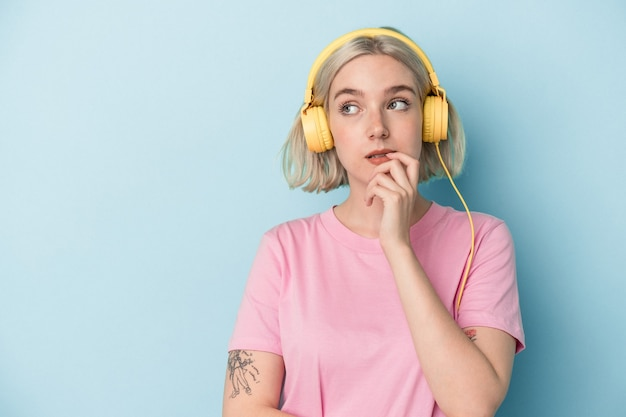 Jonge blanke vrouw luisteren naar muziek geïsoleerd op blauwe achtergrond ontspannen denken over iets kijken naar een kopie ruimte.