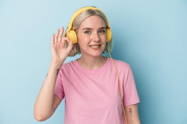 Jonge blanke vrouw luisteren naar muziek geïsoleerd op blauwe achtergrond vrolijk en zelfverzekerd weergegeven: ok gebaar.