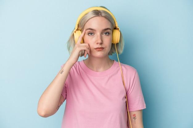 Jonge blanke vrouw luisteren naar muziek geïsoleerd op blauwe achtergrond wijzende tempel met vinger, denken, gericht op een taak.