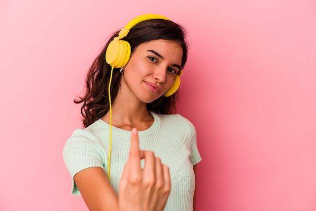 Jonge blanke vrouw luistert naar muziek geïsoleerd op roze achtergrond en wijst met de vinger naar je alsof uitnodigend dichterbij komt.