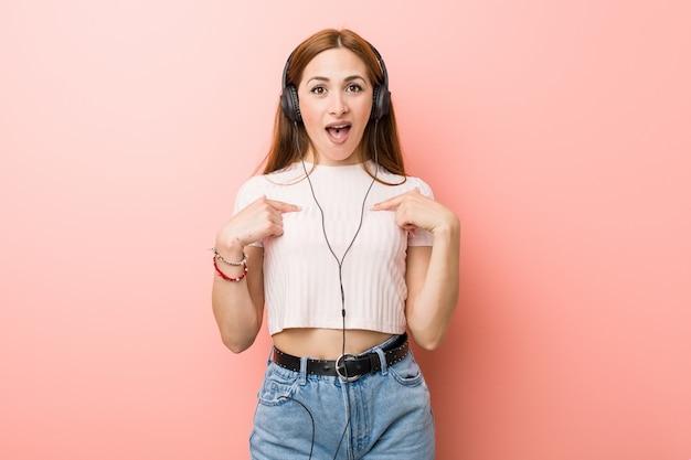 Jonge blanke vrouw luistert naar muziek verrast wijzend op zichzelf, glimlachend breed.