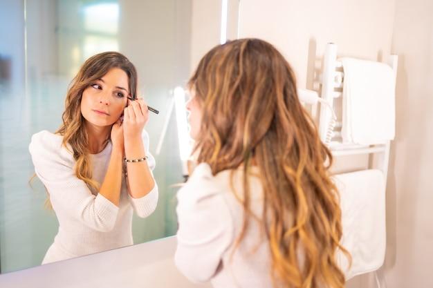 Jonge blanke vrouw maakt zich klaar en doet make-up op in de badkamer