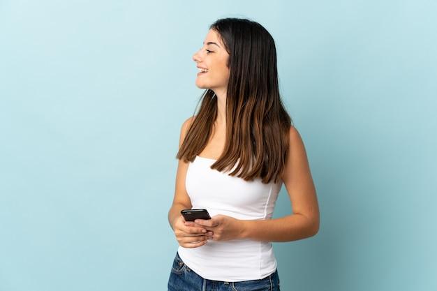 Jonge blanke vrouw met behulp van mobiele telefoon geïsoleerd op blauw lachen in zijpositie
