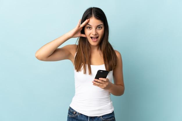 Jonge blanke vrouw met behulp van mobiele telefoon geïsoleerd op blauw met verrassing expressie